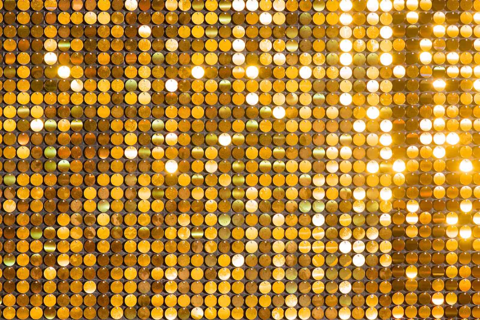Lantejoulas douradas refletindo a luz.