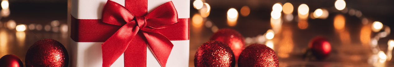 A Christmas gift tied with a red bow, surrounded by lights and baubles