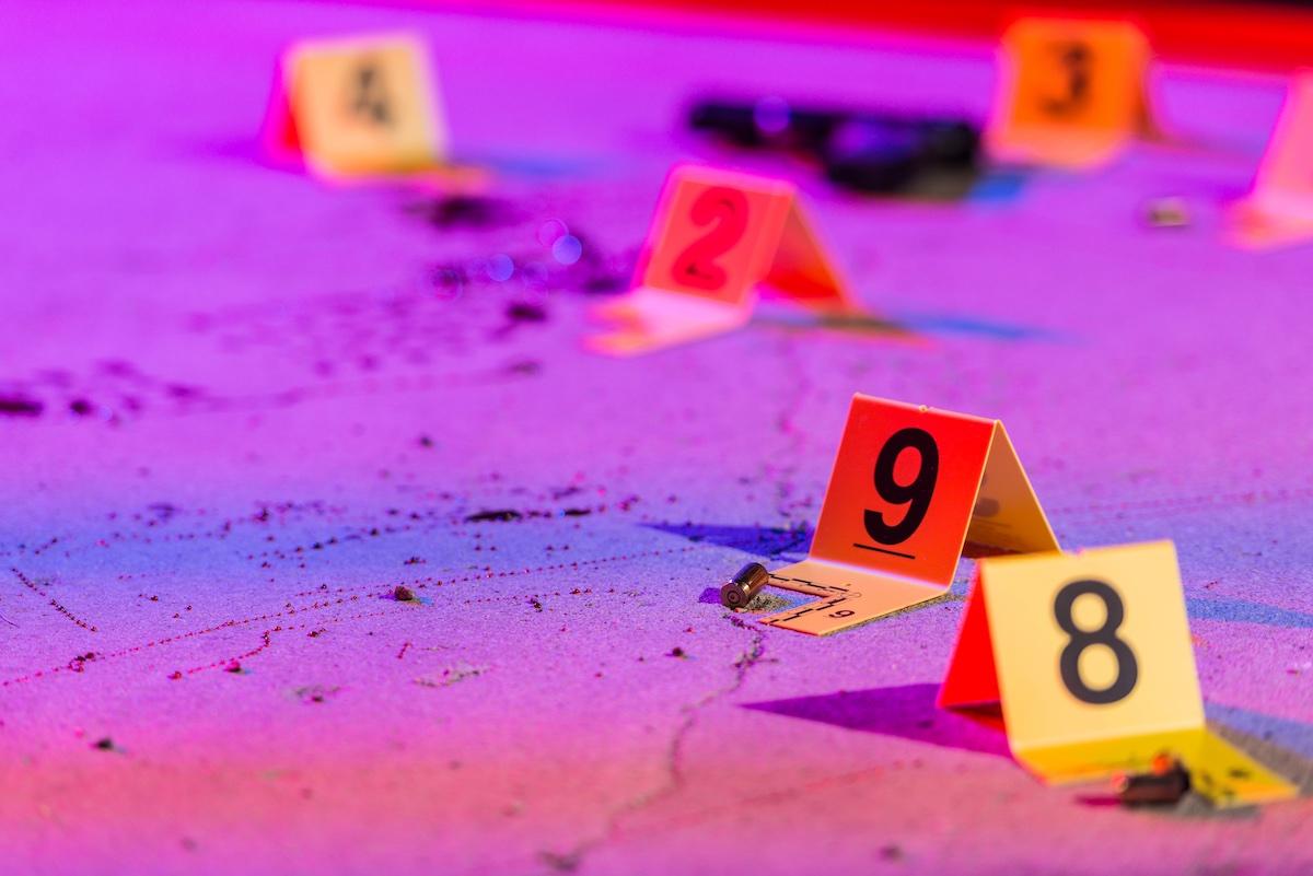 Imagem em perspectiva de placas com numerais utilizadas em cenas de crimes para sinalizar evidencias policiais. As placas são amarelas e estão posicionadas sobre o piso. Ao fundo, pode-se ver as luzes usadas em veículos de emergencia como bombeiros ou carros de polícia. Há respingos no chão de cor vermelha, semelhante a sangue. Há uma capsula de bala ao lado de uma placa amarela de evidência.