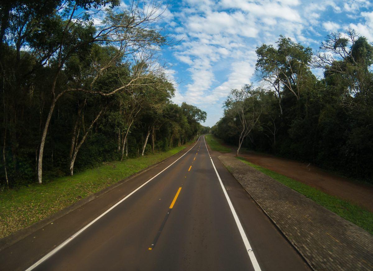 Estrada de pista simples com árvores nas margens, sob o céu azul e algumas núvens.