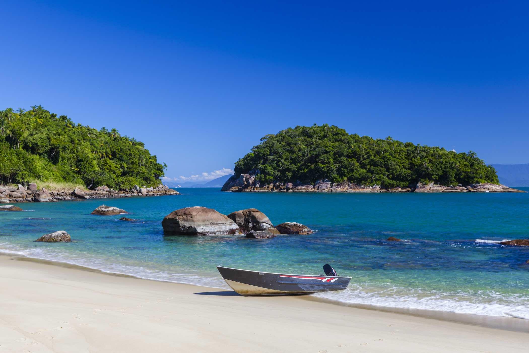 Praia de Ubatuba vazia com mar ao fundo e céu aberto.