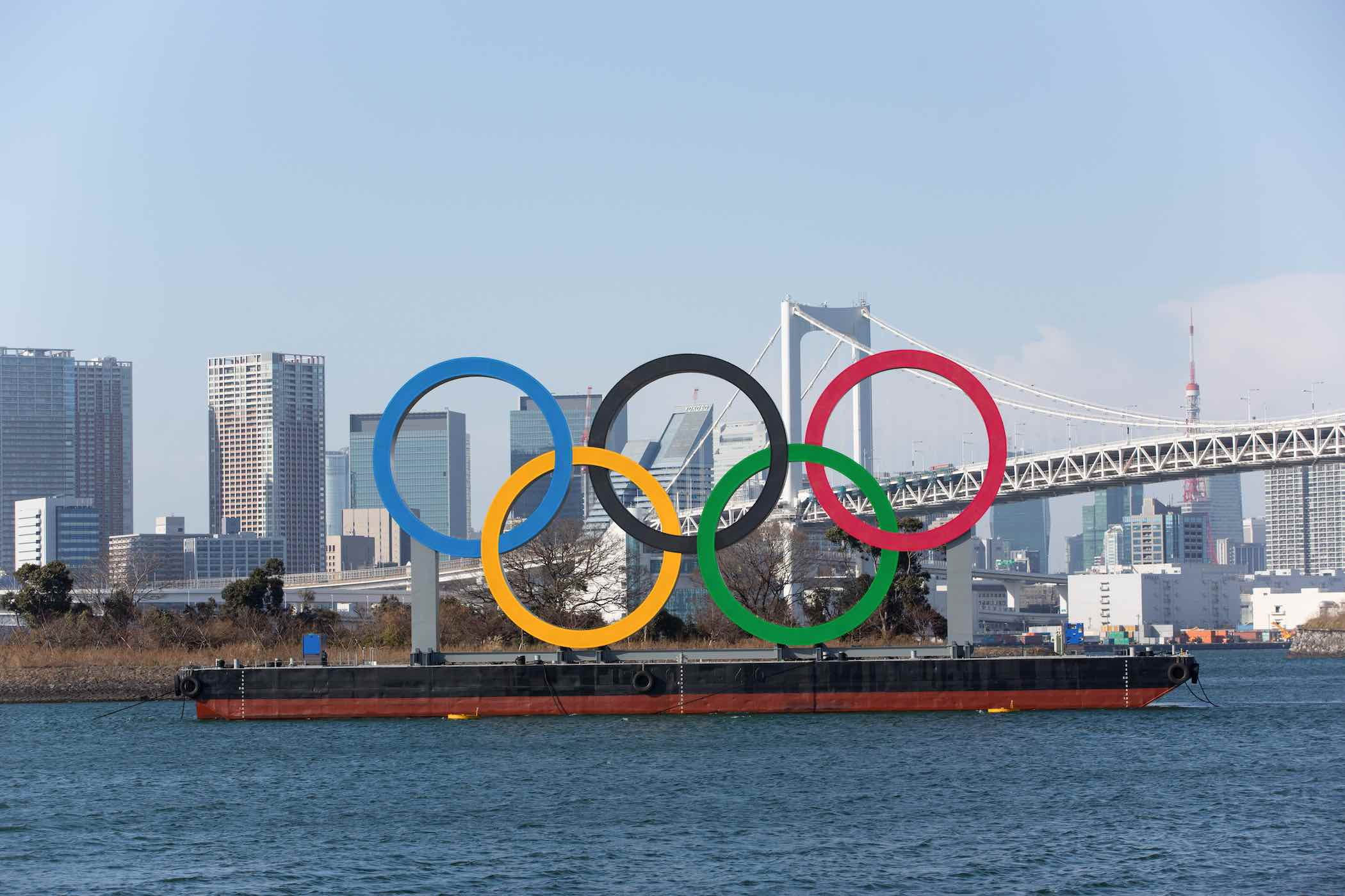 Barco carregando grandes anéis olímpicos, simbolos dos Jogos Olímpicos navega por rio com prédios de Tóquio ao fundo.