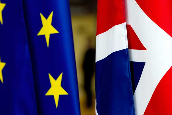 The European Union flag and the UK's Union Jack flying next to each other.