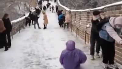 Tourist slides down Great Wall of China in icy conditions