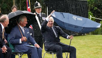 UK Prime Minister Boris Johnson can't work his umbrella and Prince Charles laughs at him: video