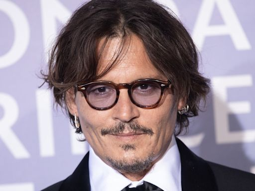 Johnny Depp poses for bizarre photo behind bars while accepting film award weeks after losing libel case