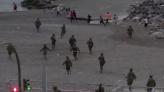 Video captures moment armed police chase thousands of Moroccan migrants who swam to Spanish enclave
