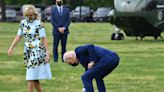 Joe Biden stops to pick a dandelion for the first lady as they walk towards Marine One for trip to Georgia