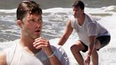 Colin Jost shows off his toned arms while surfing in the Hamptons