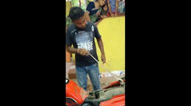 Rescuer has to unwrap cobra trapped under motorcycle seat in India