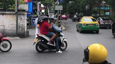 Thai man holds chair on head while sitting at back of motorcycle