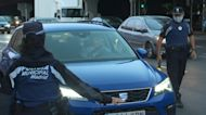 Police officers control cars as Madrid begins partial virus lockdown