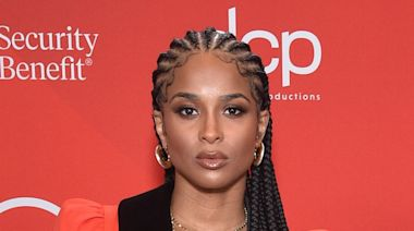 Ciara Stuns in a Cherry Red Tuxedo-Style Gown & Latex Thigh-High Boots