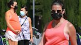 Lea Michele cradles her tank-top clad baby bump during a stroll
