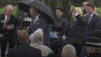 Boris Johnson struggles with umbrella at police memorial unveiling