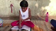 Two Indian women teach children in slum