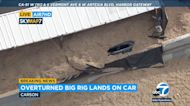 Carson: Overturned big rig lands on car, covers it with sawdust
