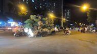 Overloaded motorcycle carries countless garbage bags on streets of Vietnam