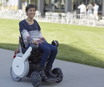 Young smiling woman using a very modern powered wheelchair to travel down a sidewalk