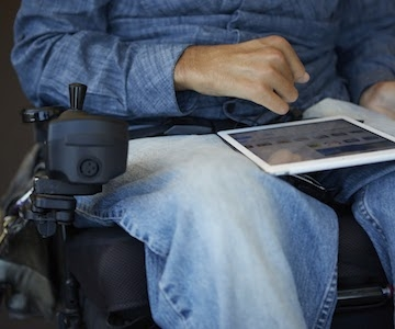 Close-up of a man using a tablet computer with the edge of his hand while sitting in a powered wheelchair
