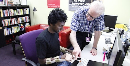 Young man typing on a computer while wearing a wrist immobilizer receiving assistance from an older man standing next to him