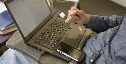 Man in wheelchair using stylus to type on laptop keyboard in his lap