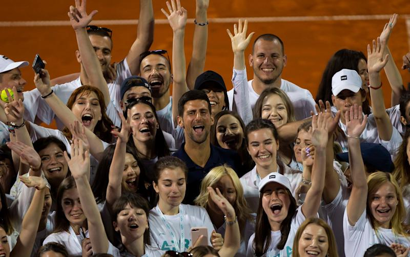 Novak Djokovic surrounded by a crowded pack of ball-kids - GETTY IMAGES