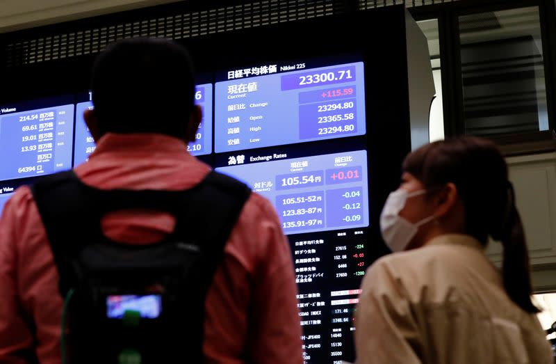 TV crews talk in front of  a large screen showing stock prices at the Tokyo Stock Exchange in Tokyo