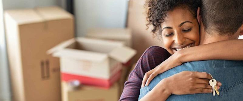 Young african woman holding home keys while hugging boyfriend