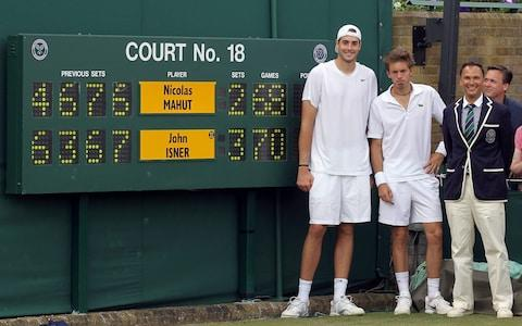 John Isner and Nicolas Mahut in front of the scoreboard after their match at Wimbledon  - Credit: Getty Images