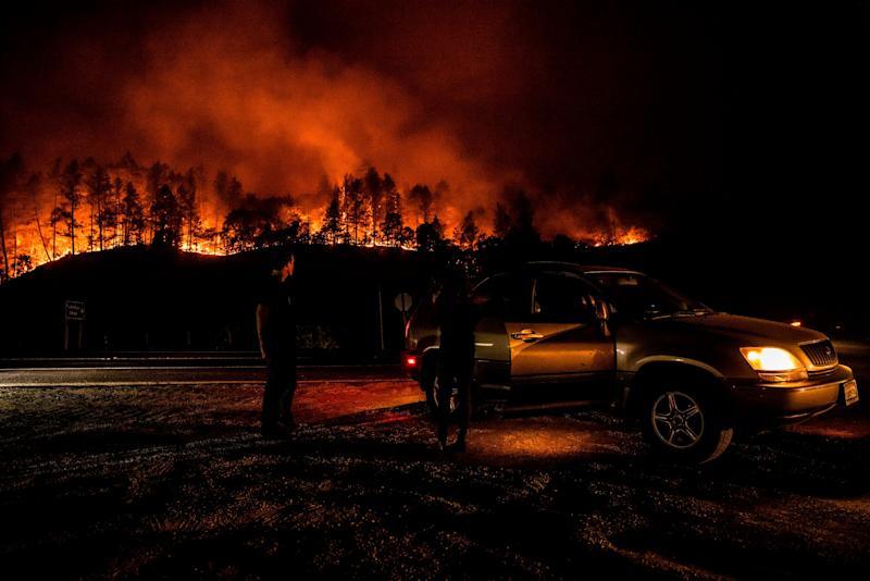 People watch the Glass Fire from the side of the road and the flames make their way down the hill near Calistoga on Monday.