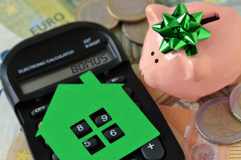 Piggy bank with calculator and paper house on euro money background - Concept of saving money to buy a home and money bonus