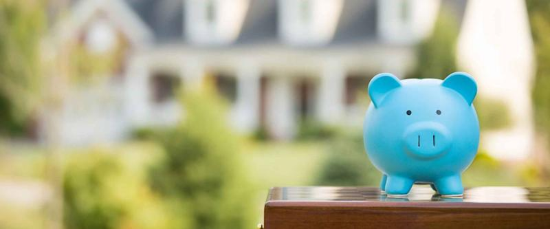 . Piggy bank isolated outside home on background. Focus on piggybank. Homeowner