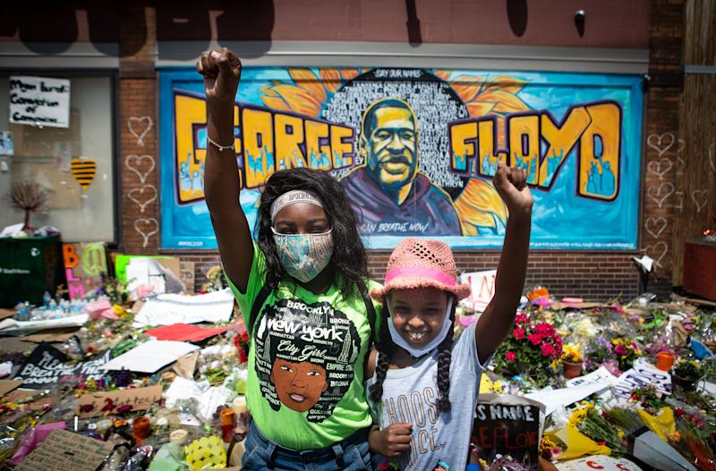 MINNEAPOLIS , MINNESOTA - JUNE 01: Two girls with fist raised pay their respects at the makeshift memorial for George Floyd at intersection in front Cup Foods where Floyd was murdered by a Minneapolis police officer on Monday, June 1, 2020 in Minneapolis , Minnesota. (Jason Armond / Los Angeles Times via Getty Images)