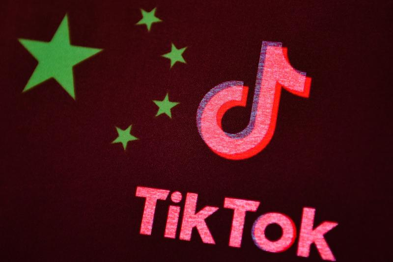 In this photo illustration a TikTok logo is seen displayed on a smartphone with a Chinese flag on the background. Photo: Getty