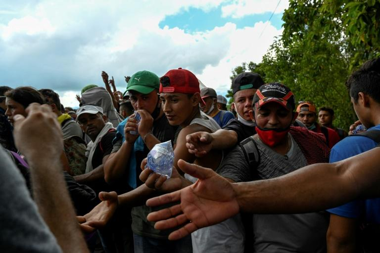 Honduran migrants, part of a caravan heading to the US, reach for water handed out by soldiers after crossing the border at Entre Rios, Guatemala on October 1, 2020