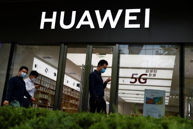 People walk past a Huawei shop, amid an outbreak of the coronavirus disease (COVID-19), in Beijing
