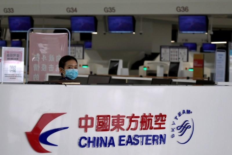 FILE PHOTO: Staff member wearing a face mask is seen behind a counter for China Eastern airlines at the Beijing Daxing International Airport, as the country is hit by an outbreak of the novel coronavirus, in Beijing