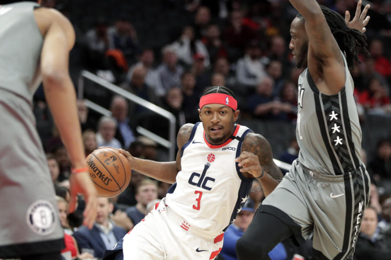 Washington Wizards' Bradley Beal (3) moves the ball past Brooklyn Nets' Taurean Prince, right, during the first half of an NBA basketball game Wednesday, Feb. 26, 2020, in Washington. (AP Photo/Luis M. Alvarez)