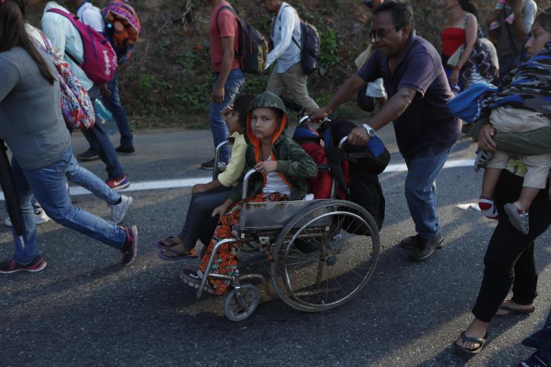 Un migrante, parte de una caravana que se dirige a la frontera entre México y Estados Unidos, empuja la silla de ruedas de un menor por la carretera en Escuintla, Chiapas, México, el sábado 20 de abril de 2019. (AP Foto/Moisés Castillo)