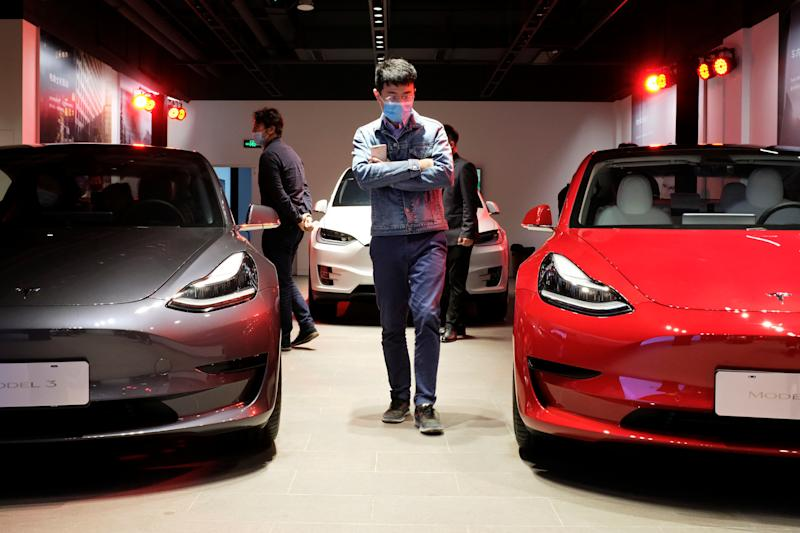 A man wearing a face mask following the coronavirus disease (COVID-19) outbreak walks by Tesla Model 3 sedans and Tesla Model X sport utility vehicle at a new Tesla showroom in Shanghai, China May 8, 2020. Picture taken May 8, 2020. REUTERS/Yilei Sun