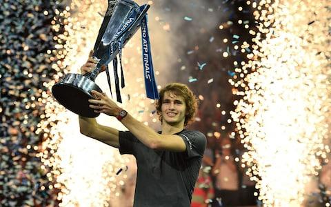 Germany's Alexander Zverev holds up the trophy after beating Serbia's Novak Djokovic in their men's singles final match on day eight of the ATP World Tour Finals tennis tournament at the O2 Arena in London on November 18, 2018. - Alexander Zverev shocked Novak Djokovic 6-4, 6-3 to win the ATP Finals on Sunday, denying the Serbian world number one a record-equalling sixth title in London. - Credit: AFP
