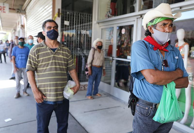 CALEXICO, CALIFORNIA - JULY 24: Faustino (R), who is currently unemployed, waits in a socially distanced line to enter a bookkeeping shop near the U.S.-Mexico border in Imperial County, which has been hard-hit by the COVID-19 pandemic, on July 24, 2020 in Calexico, California. Faustino filled out unemployment forms inside the shop. Unemployment claims in California have reached their highest levels in almost three months with surging coronavirus cases upending plans to reopen the economy. Imperial County currently suffers from the highest death rate and near-highest infection rate from COVID-19 in California. The rural county, which is 85 percent Latino, borders Mexico and Arizona and endures high poverty rates and air pollution while also being medically underserved. In California, Latinos make up about 39 percent of the population but account for 55 percent of confirmed coronavirus cases. (Photo by Mario Tama/Getty Images)