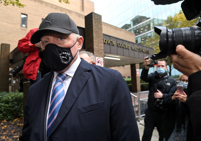 Boris Becker, in a mask, suit and baseball hat, outside of a town court building with cameras in his face.