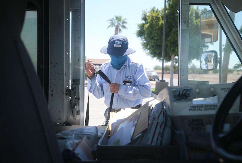 EL CENTRO, CALIFORNIA - JULY 21: A USPS postal worker wears a face mask amid the COVID-19 pandemic in hard-hit Imperial County on July 21, 2020 in El Centro, California. Imperial County currently suffers from the highest death rate and near-highest infection rate from COVID-19 in California. The rural county, which is 85 percent Latino, borders Mexico and Arizona and endures high poverty rates and air pollution while also being medically underserved. In California, Latinos make up about 39 percent of the population but account for 55 percent of confirmed coronavirus cases amid the pandemic. (Photo by Mario Tama/Getty Images)