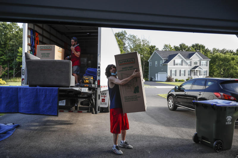 Movers unload a truckload of belongings as the Lilly family move into their new home, Tuesday, July 21, 2020, in Washingtonville, N.Y. New Yorkers anxious after weathering the worst of the coronavirus pandemic are fueling a boom in home sales and rentals around the picturesque towns and wooded hills to the north. Real estate brokers and agents describe a red-hot market recently, with many house hunters able to work from home. (AP Photo/John Minchillo)