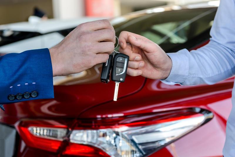 Dealer giving keys to customer in showroom