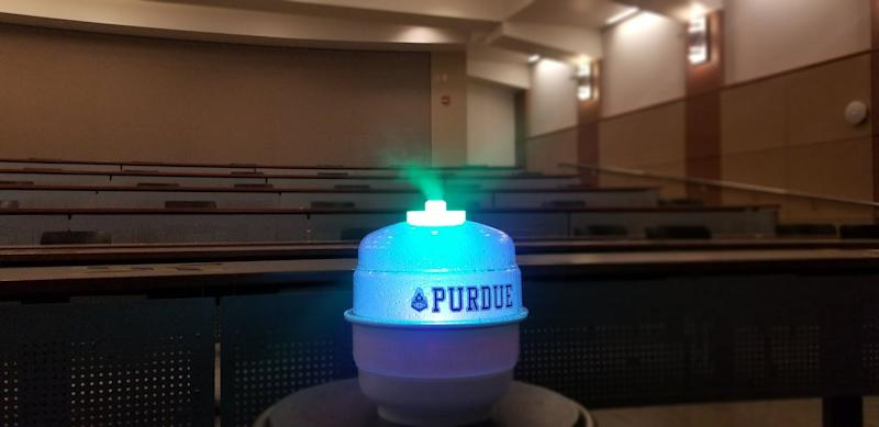A humidifier-like device dispensing mist in a classroom