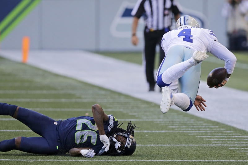 Dallas Cowboys quarterback Dak Prescott (4) goes airborne after a tackle by Seattle Seahawks cornerback Shaquill Griffin (26) during the second half of an NFL football game, Sunday, Sept. 27, 2020, in Seattle. The Seahawks won 38-31. (AP Photo/John Froschauer)