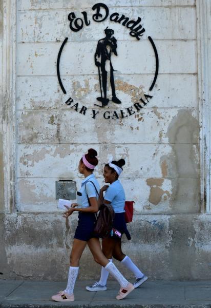 Estudiantes caminan frente al anuncio de un negocio privado, El Dandy Bar y Galería, el 3 de diciembre de 2018 en La Habana